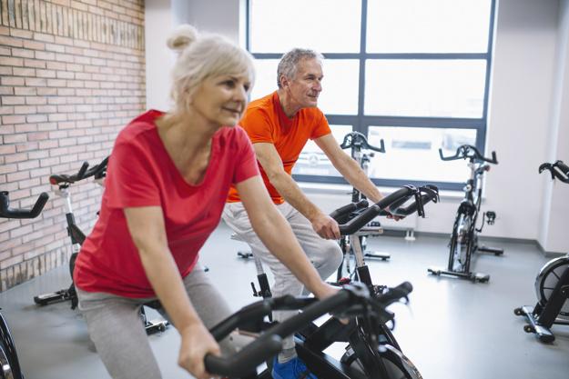 Homme et et femme faisant du vélo d'appartement